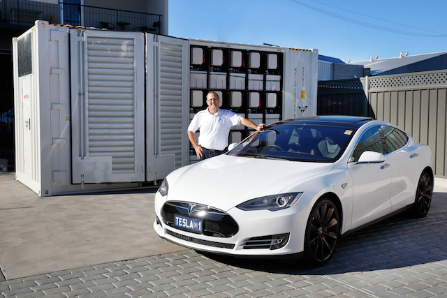 Simon Hackett with his Tesla Model S in front of the Redflow LSB